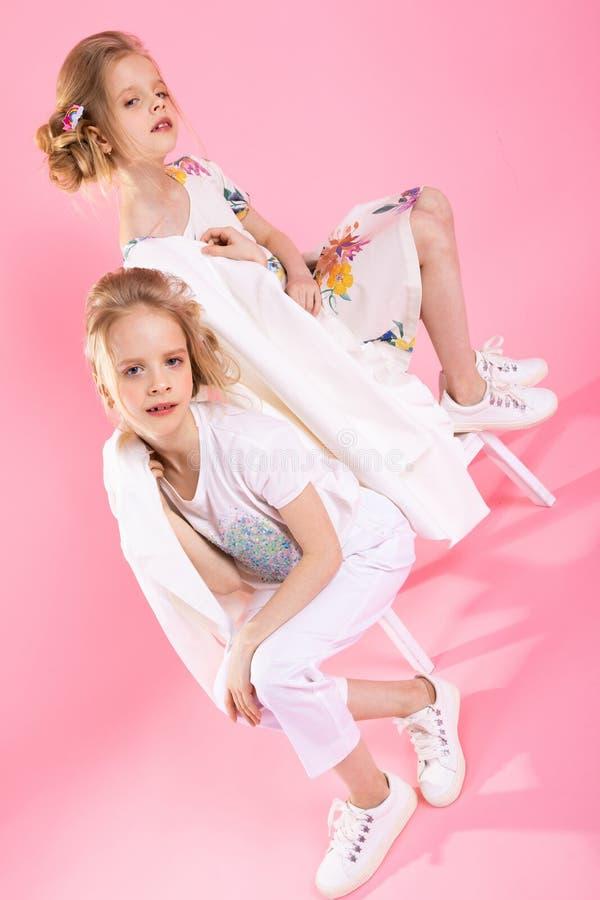 Junta meninas na roupa brilhante que levanta perto das escadas com as duas etapas em um fundo cor-de-rosa imagem de stock royalty free