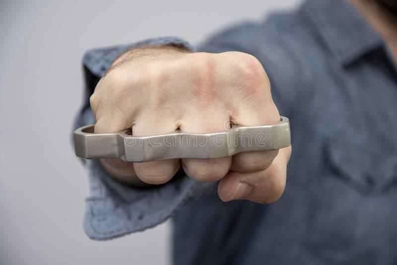Juntas de bronze do metal nas mãos de um homem, armas proibidas em uma luta imagem de stock