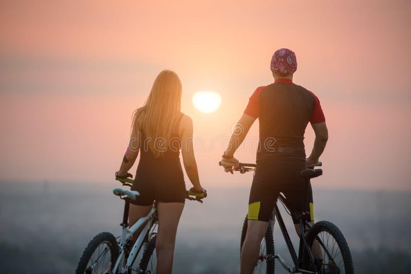 Junte al ciclista con las bicis de montaña en la colina en la puesta del sol fotos de archivo