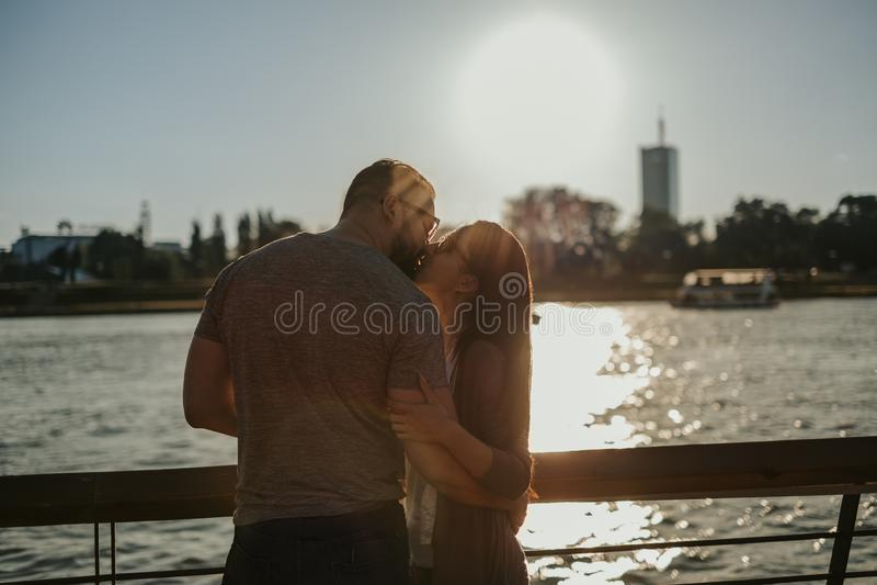 Junte besarse por el río en la puesta del sol imagenes de archivo