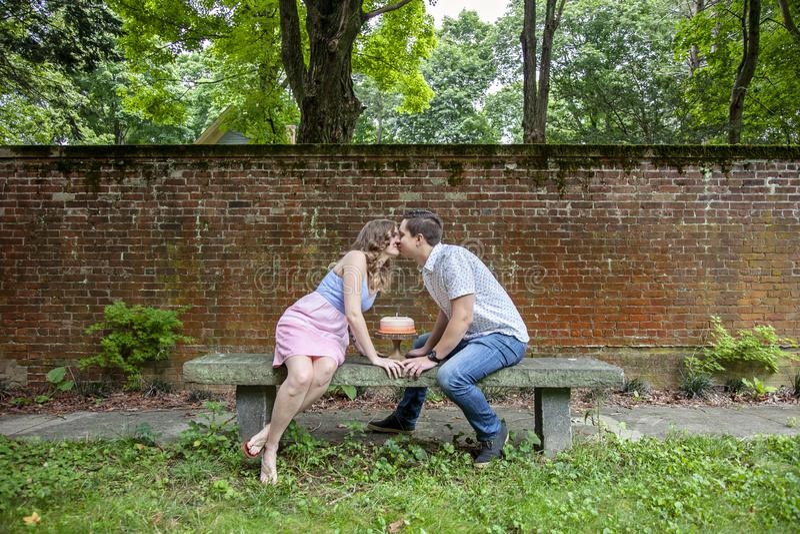 Junte besarse sobre la torta que celebra un aniversario del año imagen de archivo