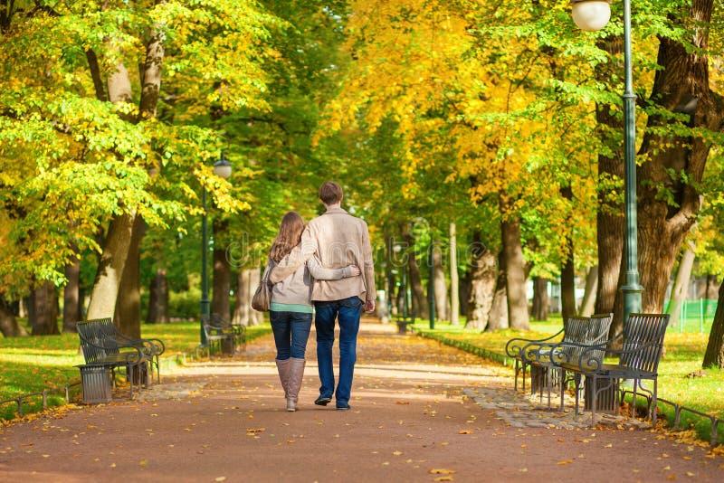 Junte caminar junto en parque en un día de la caída imagen de archivo