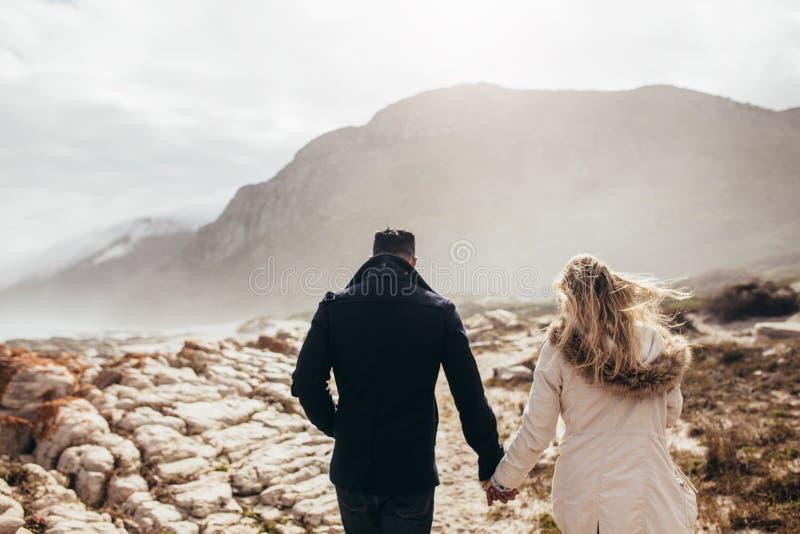 Junte caminar a través de la costa costa rocosa en un día de invierno fotografía de archivo