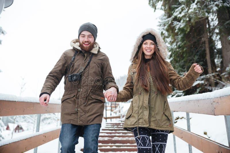 Junte celebrar las manos y el funcionamiento abajo de las escaleras en invierno imagen de archivo