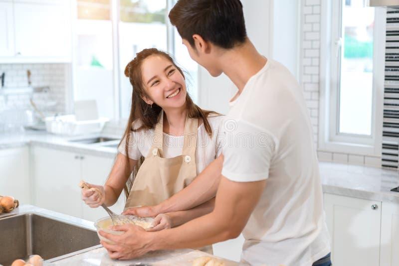 Junte cocinar la panadería en sitio de la cocina, hombre asiático joven y mujer junto fotos de archivo