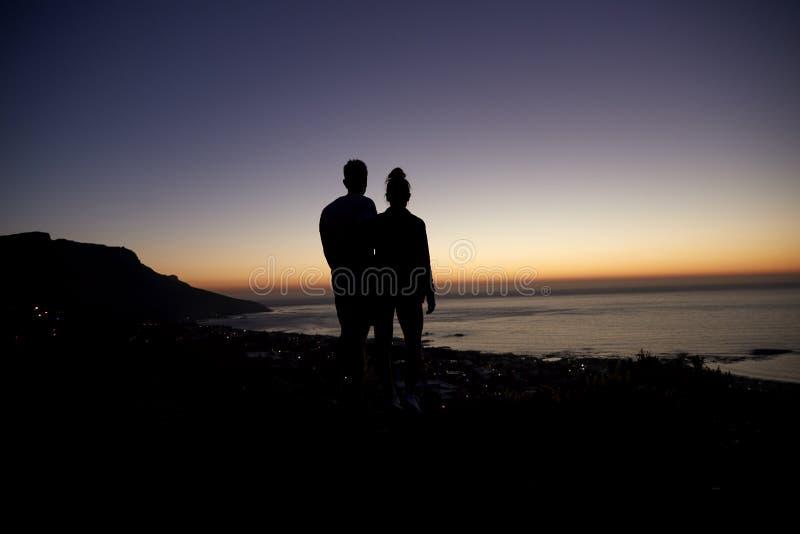 Junte dar un paseo por el mar en la puesta del sol en una playa, silueta fotos de archivo libres de regalías