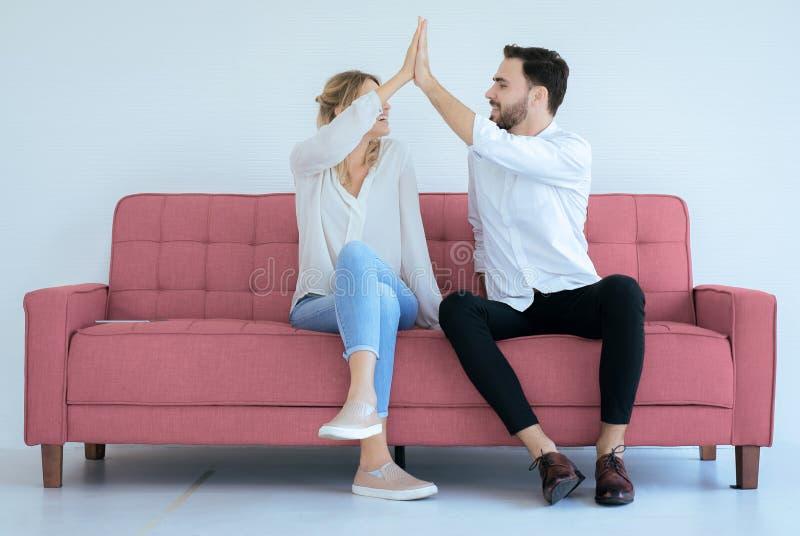 Junte del amante de manos el aplaudir feliz y el sentarse en el sofá la sensación en casa, alegre y atractiva gente imágenes de archivo libres de regalías