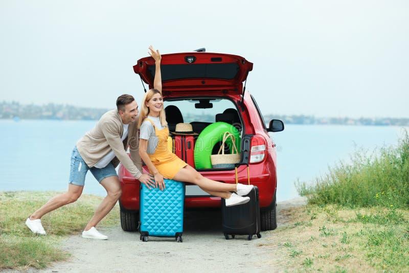 Junte divertirse cerca de tronco de coche con las maletas fotos de archivo libres de regalías