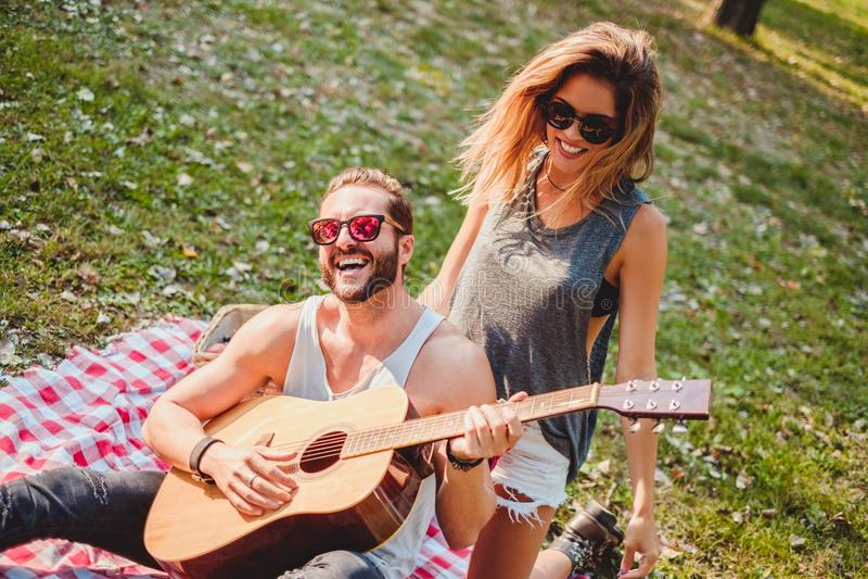 Junte divertirse con la guitarra en una comida campestre fotos de archivo