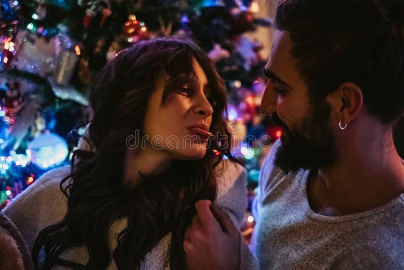 Junte divertirse delante del árbol de navidad imagen de archivo