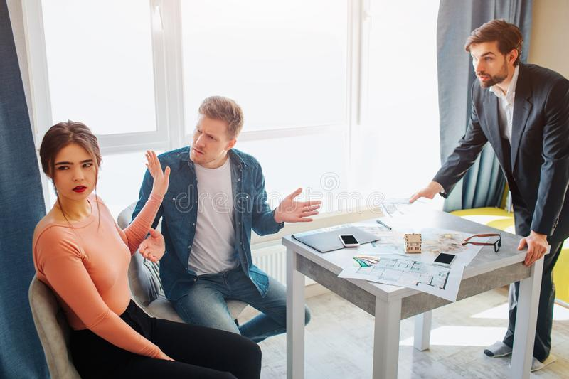 Junte el apartamento de la compra o del alquiler junto Discuten con uno a Soporte del agente inmobiliario delante de ellos e inte fotos de archivo