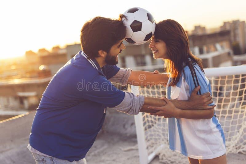 Junte el baile con un fútbol entre sus cabezas imagen de archivo