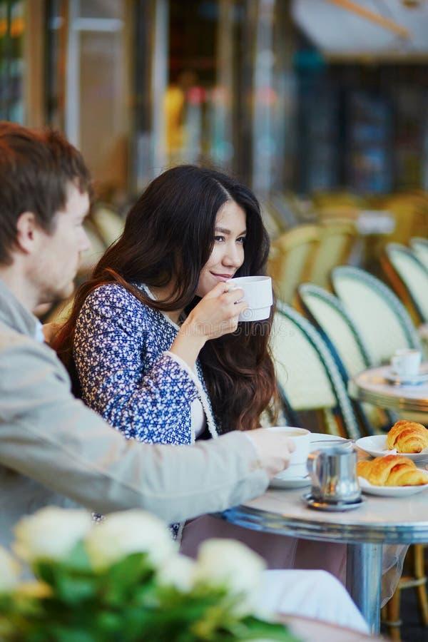 Junte el café de consumición y los cruasanes de la consumición en café parisiense imagenes de archivo