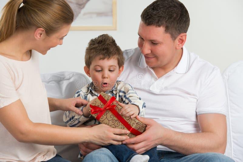 Junte el donante del regalo a su pequeño hijo en la sala de estar imagenes de archivo