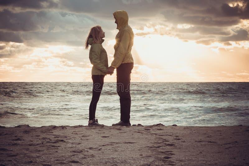 Junte el hombre y a la mujer en el amor que se coloca en la playa de la playa foto de archivo