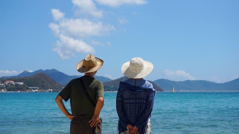 Junte el hombre y a la mujer que permanecen en la playa y la mirada de la playa lejos imagen de archivo libre de regalías