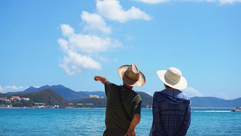 Junte el hombre y a la mujer que permanecen en la playa y la mirada de la playa lejos imagen de archivo