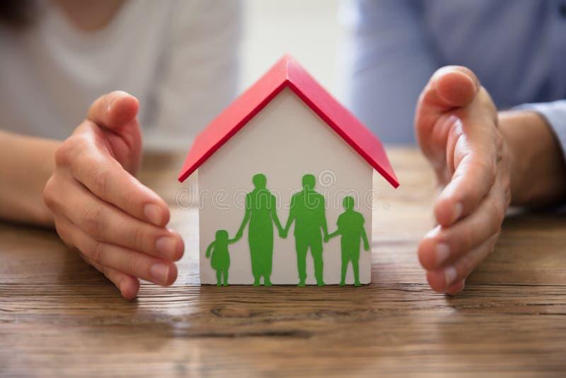Junte el papel de protección de la familia cortado y el modelo de la casa foto de archivo