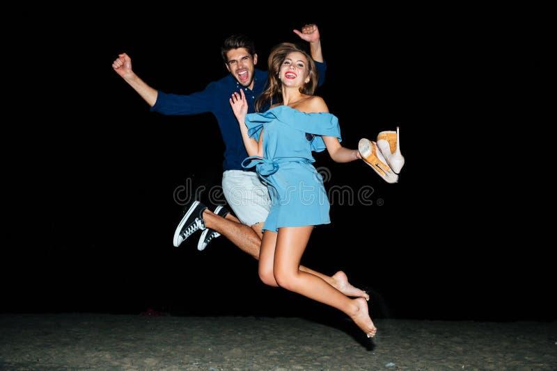 Junte el salto en el aire en la playa en la noche imagen de archivo libre de regalías