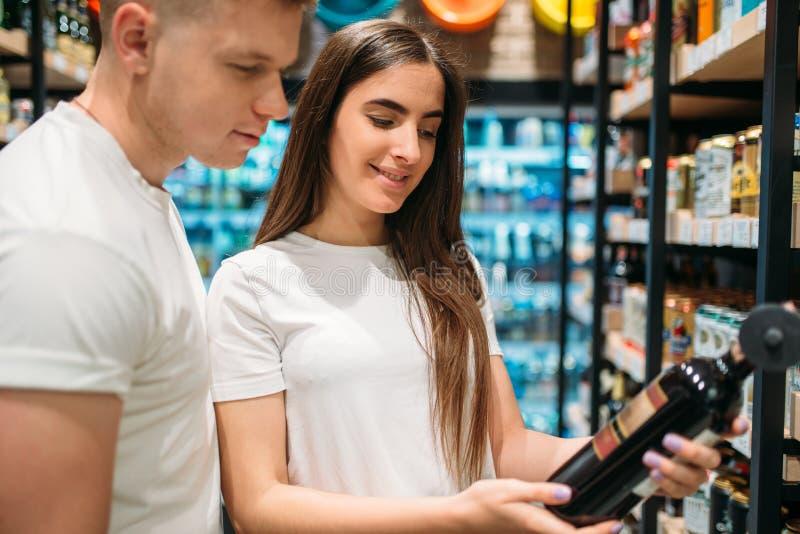 Junte elegir el vino en la sección del alcohol en mercado fotografía de archivo libre de regalías