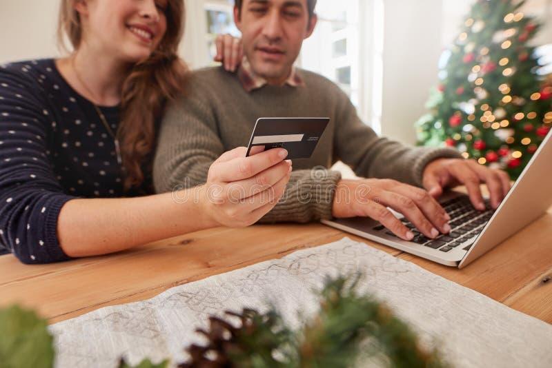 Junte hacer compras en línea para la Navidad con la tarjeta de crédito y el ordenador portátil imágenes de archivo libres de regalías