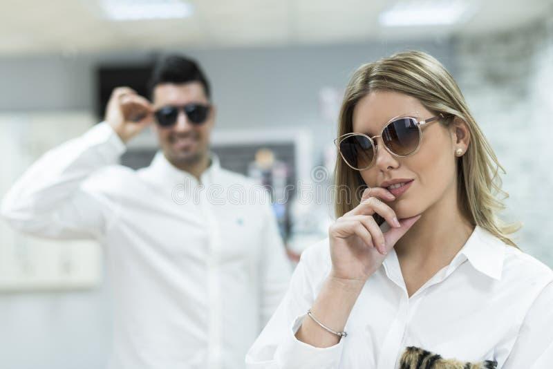 Junte intentar en las gafas de sol en tienda óptica de las lentes fotografía de archivo libre de regalías