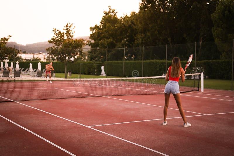 Junte jugar a tenis en la corte fotografía de archivo