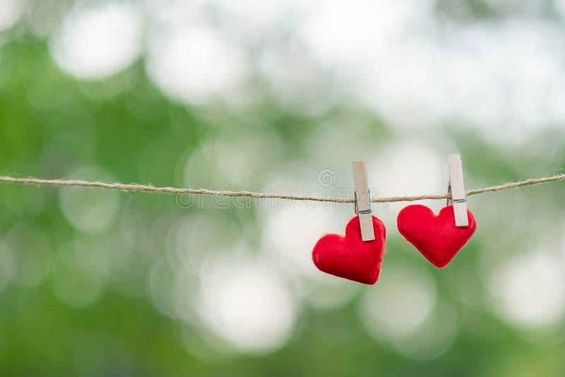 Junte la decoración roja de la forma del corazón que cuelga en línea con el espacio de la copia para el texto en fondo verde de l imagenes de archivo