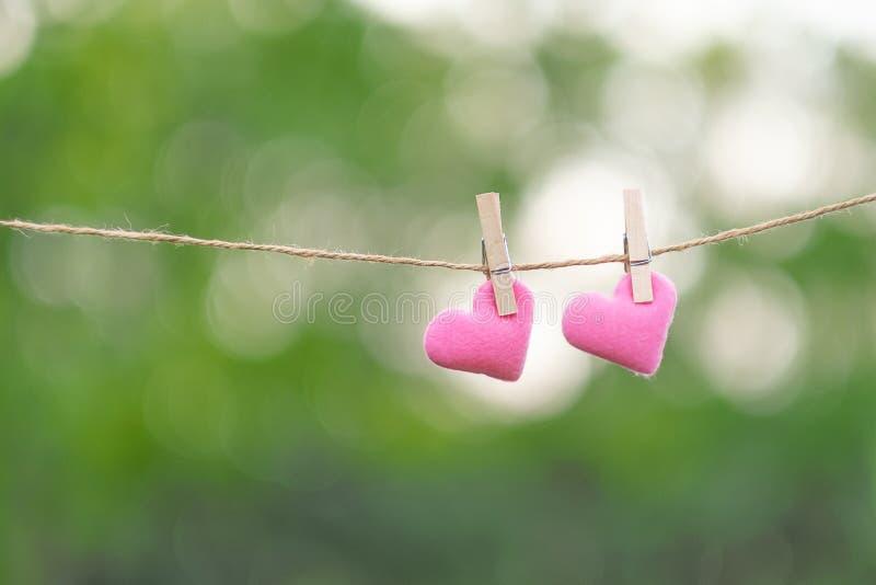 Junte la decoración rosada de la forma del corazón que cuelga en línea con el espacio de la copia para el texto en fondo verde de fotografía de archivo
