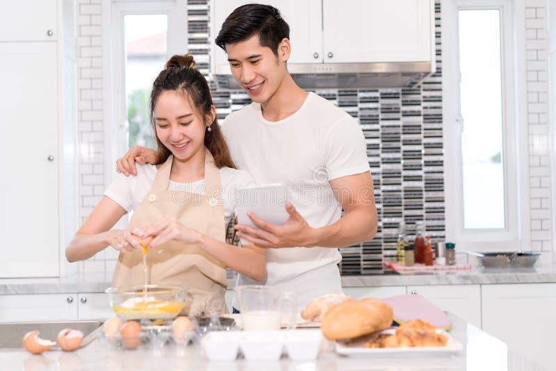 Junte la fabricación de la panadería, de la torta en sitio de la cocina, del hombre asiático joven y de la mujer fotos de archivo libres de regalías