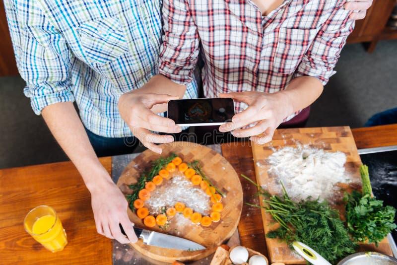 Junte la fabricación del corazón con las zanahorias y tomar imágenes usando smartphone imagen de archivo libre de regalías