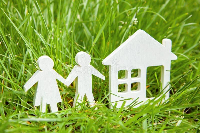 Junte a la familia joven del hombre y de la mujer cerca del sueño casero en hierba verde Construcción de una casa de los material fotos de archivo