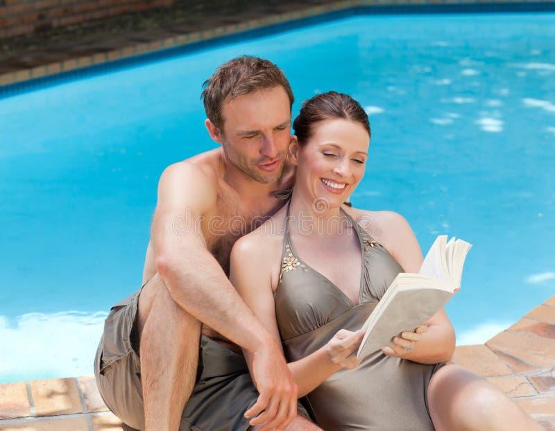 Junte la lectura de un libro al lado de la piscina imagen de archivo libre de regalías
