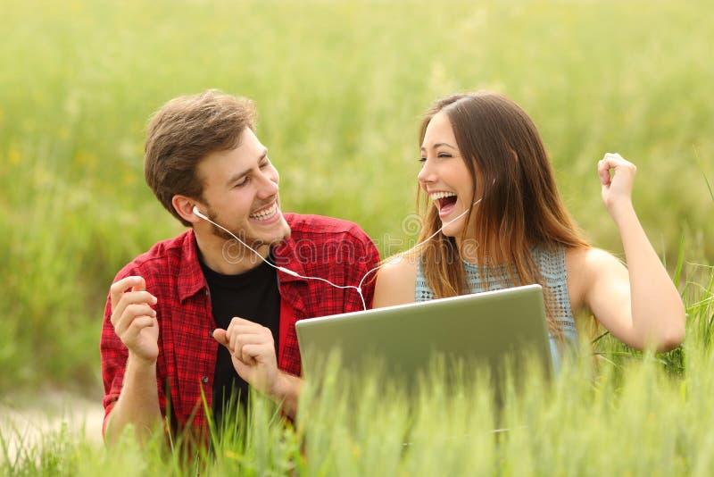 Junte la música cantante y que escucha de un ordenador portátil fotografía de archivo libre de regalías