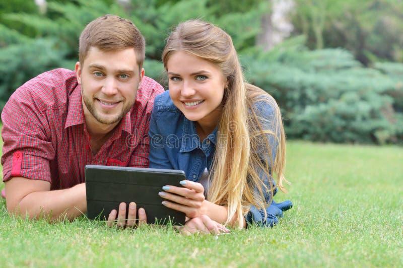 Junte la mentira en parque usando la PC de la tableta junto en un día soleado imagen de archivo libre de regalías