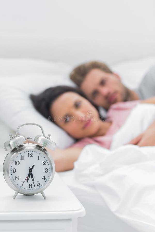 Junte la mentira en su cama al lado de un despertador foto de archivo libre de regalías