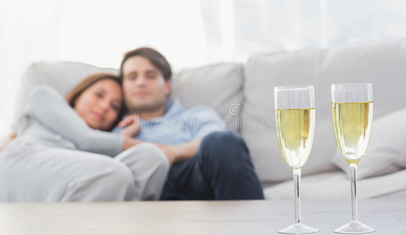 Junte la relajación en un sofá con las flautas del champán foto de archivo