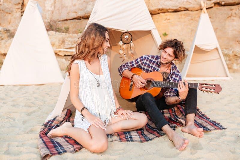 Junte la relajación y tocar de la guitarra en tienda india en la playa imágenes de archivo libres de regalías