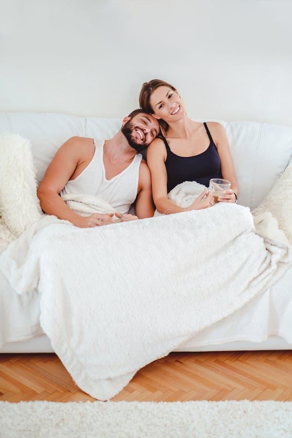 Junte la sonrisa en el sofá y sostener el café imágenes de archivo libres de regalías