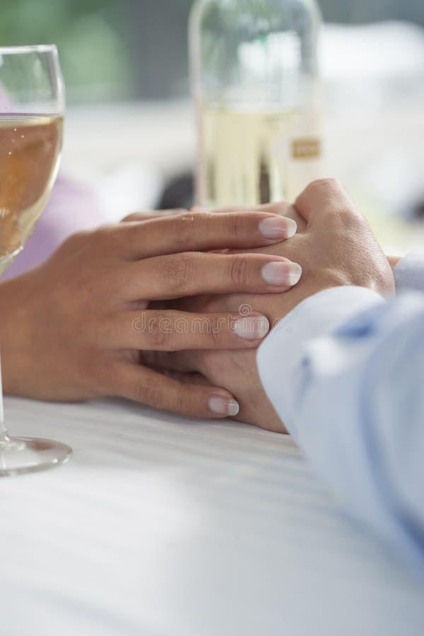 Junte llevar a cabo las manos y la consumición del vino blanco en café al aire libre foto de archivo libre de regalías