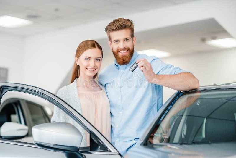Junte llevar a cabo llave y la situación del coche en el coche en salón de la representación fotografía de archivo