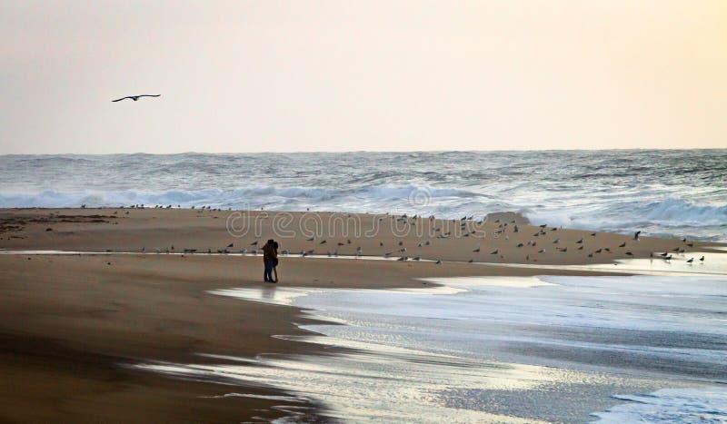 Junte los abrazos en la playa cerca del agua foto de archivo libre de regalías