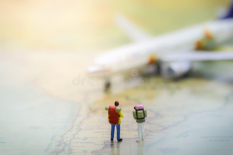 Junte a los backpackers que se colocan en mapa del mundo del vintage con el aeroplano foto de archivo