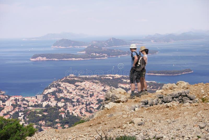 Junte a los caminantes que miran gran paisaje marino fotografía de archivo