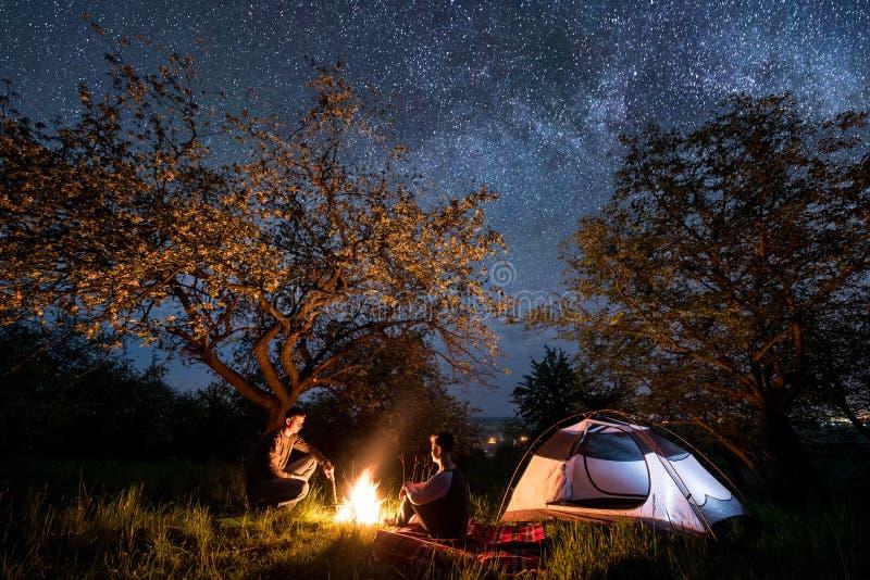 Junte a los caminantes que se sientan en una hoguera cerca de la tienda debajo de árboles y del cielo nocturno hermoso por comple imagen de archivo
