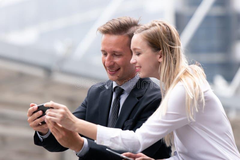 Junte a los hombres de negocios que miran smartphone junto y sonría al aire libre foto de archivo