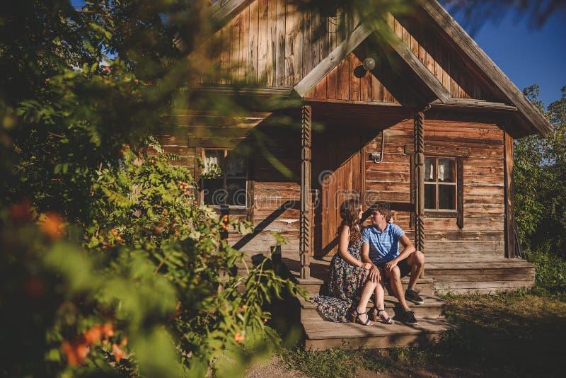 Junte los hombres y a las mujeres en el pueblo, cerca de una casa de madera Estilo rural Verano rústico fotografía de archivo libre de regalías