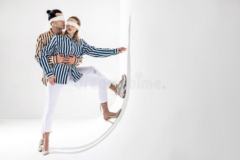 Junte los pantalones blancos que llevan que presentan cerca de la pared blanca en vendas imagen de archivo libre de regalías