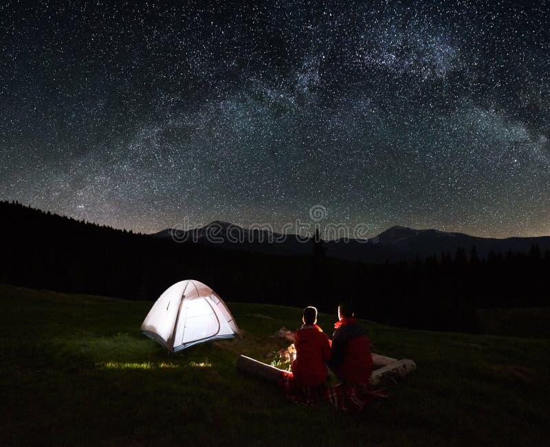 Junte a los turistas cerca de hoguera y de tiendas debajo del cielo nocturno por completo de estrellas y de la vía láctea imagenes de archivo