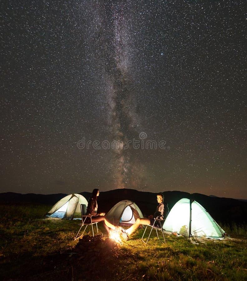 Junte a los turistas en el campo de la noche en montañas debajo del cielo estrellado fotos de archivo